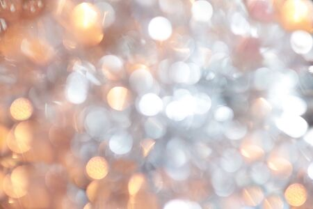 Golden christmas background and new year concept, abstract defocused light background with bokeh and blur. Winter banner for your text, background image or overlay layer in the photo editor, out of focus