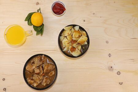 Meat goulash in a dark cup, stewed potato stew and a mug with lemon juice, the basis of diet food, protein diet, close-up, top view, rustic style. Grilled meat with sauce, place for text and recipe, delicious nutritious dinner 版權商用圖片