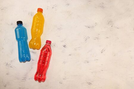 Isotonic energy drink in blue, yellow and red bottles on a concrete table, sports drinks to maintain body tone during workouts that support optimal hydration and vitality
