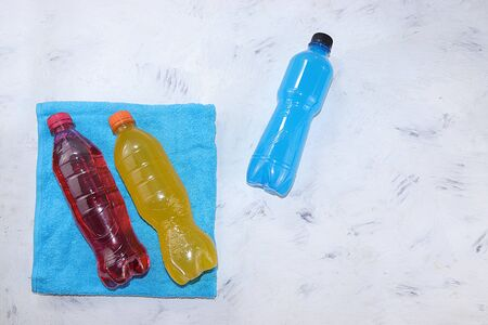 Isotonic energy drink in blue, yellow and red bottles on towels, sports drinks to maintain body tone during workouts on a concrete table that support optimal hydration and vitality