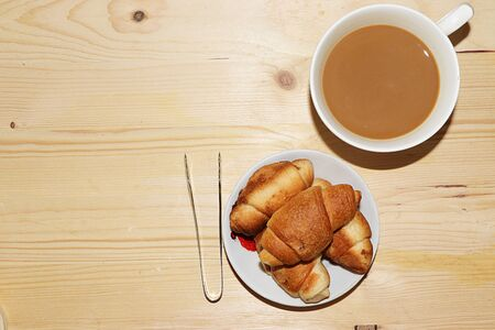 Cup of coffee with milk and fresh ruddy croissants on a wooden table, top view, place for text. The concept of a modern bakery. Tasty traditional breakfast. Foto de archivo - 135461548