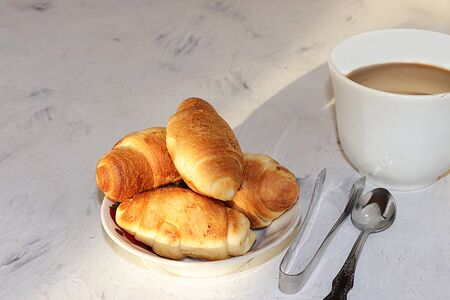 Cup of coffee with milk and fresh ruddy croissants on a gray table with, place for text. The concept of a modern bakery. Tasty traditional breakfast. Foto de archivo - 135461558