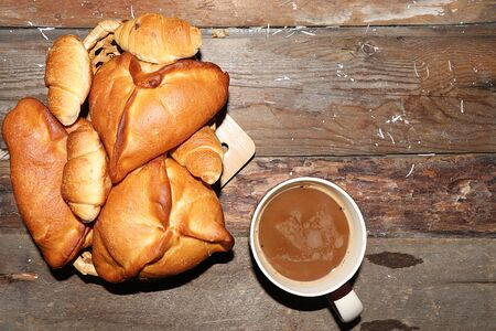 Homemade Russian pies with filling on an old wooden table and a cup of latte coffee, top view, place for a recipe. Traditional rustic style, natural food Foto de archivo - 135461770