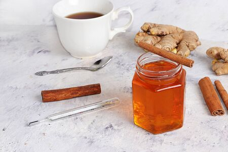 A healthy drink of hot tea with ginger root, cinnamon sticks, honey, a thermometer, spices for Ayurvedic medicine. Alternative medicine concept, has a strong anti-inflammatory effect, detoxification of the body,