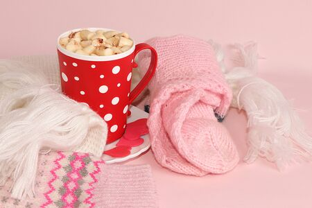 Modern woman's table with a cup of cocoa, a scarf, socks, pink background, the concept of winter comfort and the Hygge style, warm clothes and a hot drink