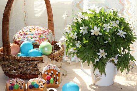 Easter composition on a sunny rustic table. Happy blue eggs in a basket, Easter cake and sweets, spring flowers. Foto de archivo - 139996010