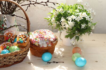 Easter composition on a sunny rustic table. Happy blue eggs in a basket, Easter cake and sweets, spring flowers. Foto de archivo - 139996012