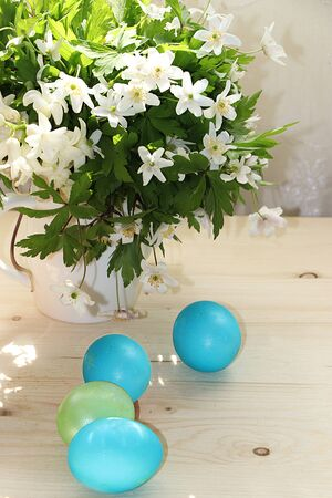 Easter composition on a sunny rustic table. Happy blue eggs and flowers. Spring festive background. Foto de archivo - 139996011