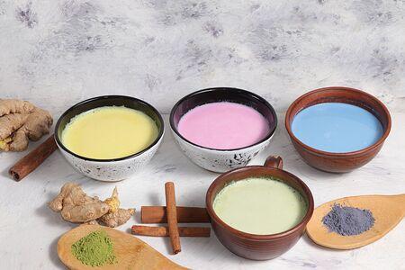 An assortment of colorful latte Japanese tea, matcha green, blue, pink moon milk, golden milk, ginger and cinnamon, top view. Foto de archivo - 139996014