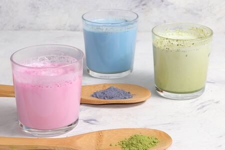 An assortment of colorful latte Japanese tea, matcha green, blue, pink moon milk. A fashionable healthy drink has anti-inflammatory properties, Foto de archivo - 139996018