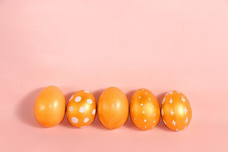 Decorated golden easter eggs on a pink background. Minimal holiday concept. Happy easter background. Creative painting of eggs at home, the idea of simple drawings for coloring, a place for text, a postcard, Foto de archivo - 139530254