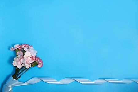 Carnations on a blue background. Creative modern bouquet, minimal holiday concept. Postcard for Women's Day or Valentine's Day, birthday greetings, wedding, Foto de archivo - 139688952