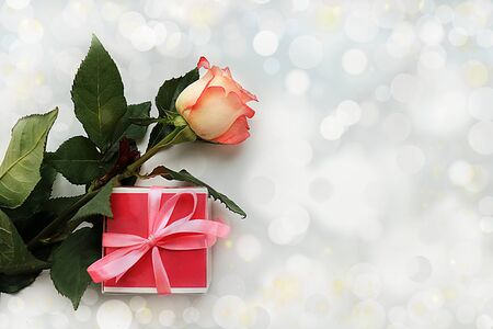 Greeting card for Women's Day or Valentine's Day. Red rose and gift box on abstract blurred background with bokeh. March 8 festive background, place for text, banner. Happy birthday, wedding. Foto de archivo - 139689032