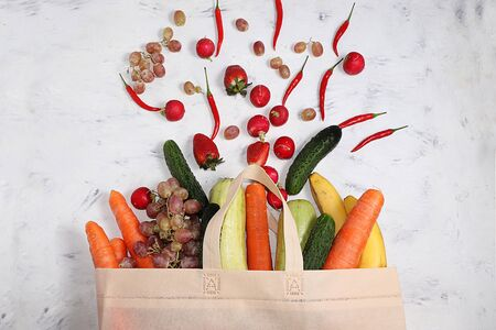 Useful natural products in an eco bag, the concept of a healthy lifestyle, zero waste. Vegetables, fruits, nuts, eggs and bread rolls in tissue packaging, diet food, flat lay. Foto de archivo - 139690798