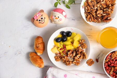 Healthy breakfast, fun food for children. The concept of healthy and natural food. Oatmeal with granola or granola, grapes, nuts and croissants, top view, Foto de archivo - 139996067
