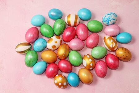 Decorated golden easter eggs on a pink background. Minimal holiday concept. Happy easter background. Creative painting of eggs at home, the idea of simple drawings for coloring, a place for text, a postcard, Foto de archivo - 139976496
