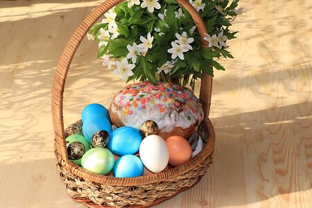 Easter composition on a sunny rustic table. Happy blue eggs in the basket, Easter cake and sweets, spring flowers, rustic style, minimalism. Spring holiday Foto de archivo - 140135608