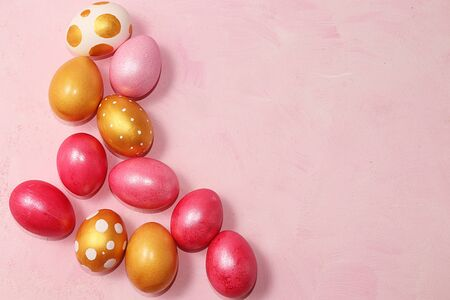 Decorated golden easter eggs on a pink background. Minimal holiday concept. Happy easter background. Creative painting of eggs at home, the idea of simple drawings for coloring, a place for text, a postcard, Foto de archivo - 141423925