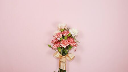 Carnations on a pink table, abstract spring floral background. Creative modern bouquet, minimal holiday concept. Greeting card for Women's Day or Mother's Day, happy birthday, wedding, gift for loved ones, place for text, Foto de archivo - 141427168