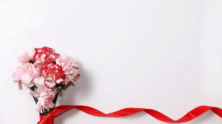 Carnations on a white table, abstract spring floral background. Creative modern bouquet, minimal holiday concept. Greeting card for Women's Day or Mother's Day, happy birthday, wedding, gift for loved ones, place for text, Foto de archivo - 141426940