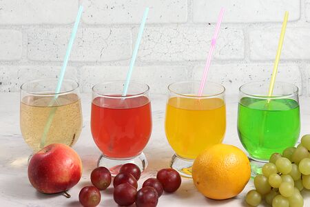 Fruit cider, juices or fruit drinks in glasses and ingredients on a sunny table. The concept of a detox diet and weight loss, healthy and natural nutrition, bar. Healthy breakfast, place for text, lifestyle.