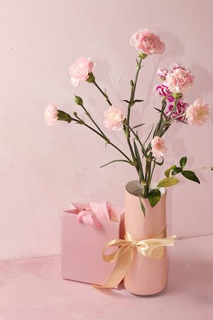 Carnations with a gift on a pink table, abstract spring floral background. Creative modern bouquet, minimal holiday concept. Greeting card for Women's Day or Mother's Day, happy birthday, wedding, gift for loved ones, place for text, Foto de archivo - 141426950