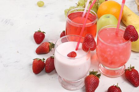 Strawberry smoothie, smoothie, juice or fruit drinks in glasses and ingredients on a sunny table. The concept of detox diet and weight loss, healthy and natural nutrition, bar. Healthy breakfast, lifestyle Foto de archivo - 141655653