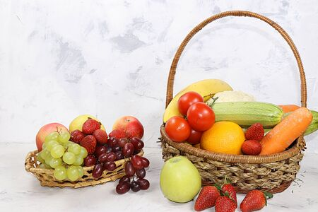 Fruits and vegetables in baskets on a concrete table. The concept of detox diet and weight loss, healthy and natural nutrition. Healthy breakfast, lifestyle. Foto de archivo - 141657935