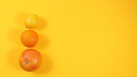 Summer banner, citrus fruits, grapefruit, orange, lemon on a bright yellow background, minimal concept of relaxation and detox, diet and weight loss. Place for text, Foto de archivo - 142010622