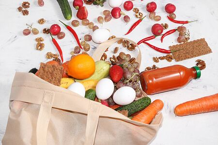 Useful natural products in an eco-friendly bag, the concept of a healthy lifestyle and weight loss, zero waste. Vegetables, fruits, nuts, eggs and rolls in fabric packaging, diet food, flat lay. Foto de archivo - 142454811