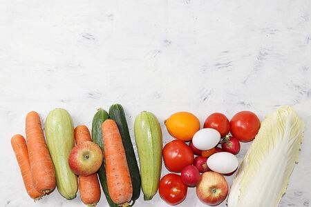 Useful natural products on a concrete table, healthy lifestyle concept. Vegetables, fruits, nuts, eggs and bread, diet food ingredients, Foto de archivo - 142454816