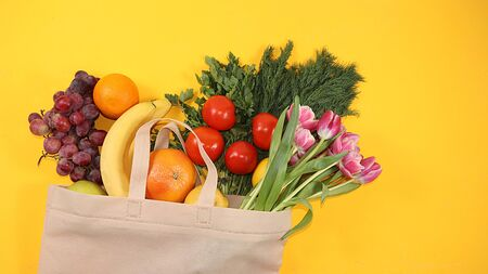 Healthy natural products in an eco bag on a bright background, the concept of a healthy lifestyle and weight loss, zero waste. Vegetables, fruits, apples and greens in cloth packaging, diet, body detox, flat lay. Banner for the screen and the store. No plastic.