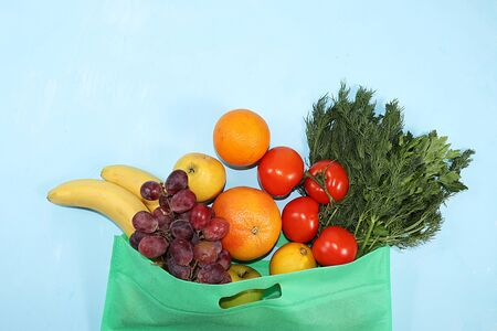 Healthy natural products in an eco bag on a bright background, the concept of a healthy lifestyle and weight loss, zero waste. Vegetables, fruits, apples and greens in cloth packaging, diet, body detox, flat lay. Banner for the screen and the store. No plastic. Foto de archivo - 142454814