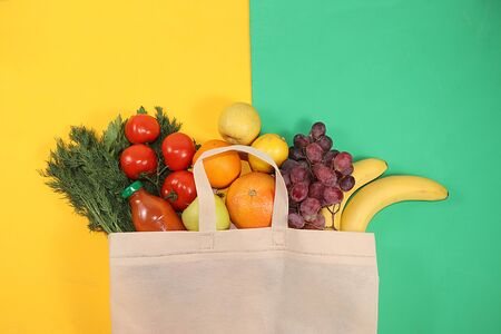 Healthy natural products in an eco bag on a bright background, the concept of a healthy lifestyle and weight loss, zero waste. Vegetables, fruits, apples and greens in cloth packaging, diet, body detox, flat lay. Banner for the screen and the store. No plastic. Foto de archivo - 142454823
