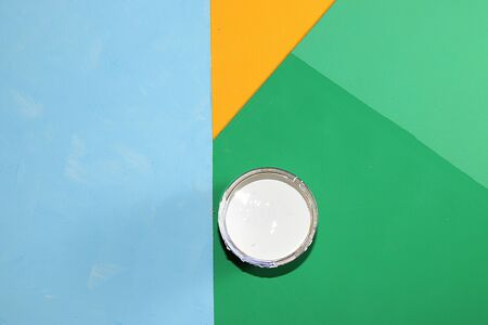 Can of paint for repair on a multi-colored painted background. Banner for the shop, geometry. Minimal concept of renovation and construction. Top view, place for text. Fashionable green, blue, Foto de archivo - 142101891