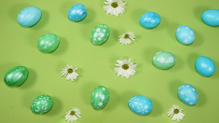 Decorated golden and blue eggs on a trendy green background. Minimal holiday concept. Happy Easter background, pattern, greeting card, banner for the screen. Foto de archivo - 142323114