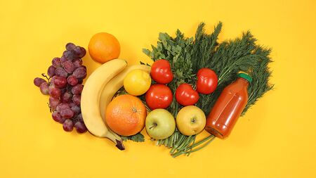 Healthy organic food on a yellow table, healthy lifestyle concept. Vegetables, fruits, grapes, herbs, bananas, citrus fruits, diet ingredients, flat lay, Foto de archivo - 142323014