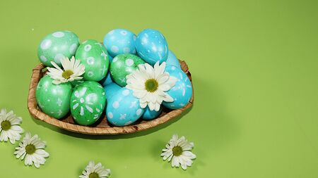 Decorated golden and blue eggs on a trendy green background. Minimal holiday concept. Happy Easter background, place for text, postcard, banner for the screen. Foto de archivo - 142416999