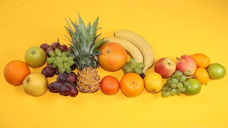 Summer banner, citrus fruits, grapefruit, orange, lemon, bananas on a yellow background, minimal concept of relaxation, diet, healthy food. Place for text, flat lay,