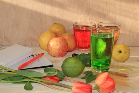 Apple cider, juice or fruit drink in a glass and a notebook on a sunny table. The concept of diet and weight loss. increasing the body's immune defense against viruses and colds,