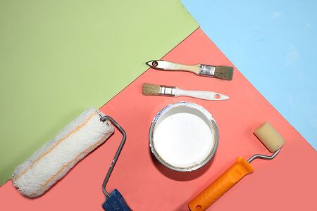 Repair tools on a multi-colored painted background. Shop banner, geometry. Minimal renovation and construction concept. Top view,. Trendy green, blue, pink color.