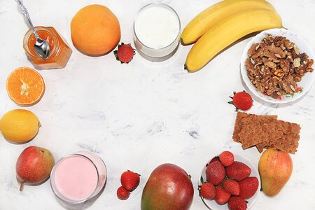 Useful breakfast. Strawberry smoothie, cocktail, granola, fresh berries and fruits, bananas, mangoes and pears on a gray concrete background. The concept of healthy and natural food, detox diet, food for children,