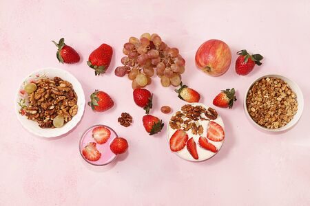Useful breakfast. Strawberry smoothie, cocktail, granola, fresh berries and grapes on a pink concrete background. The concept of healthy and natural food, detox diet, food for children, rustic style.