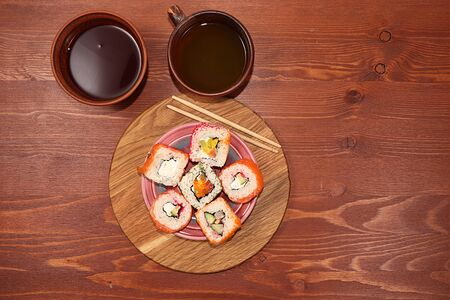 Fresh sushi rolls with sauce on a wooden table, , copy space. Japanese cuisine concept