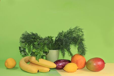 Dill, fruits, vegetables and parsley on a green background. The concept of healthy and natural foods to enhance immunity, a healthy lifestyle and weight loss, vitamins. banner