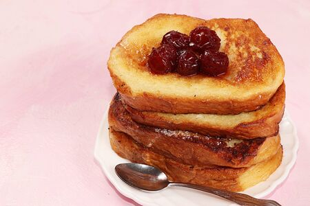 French toasts on a pink table with breadcrumbs. Fried bread with milk and scrambled eggs, concept of a modern bakery.