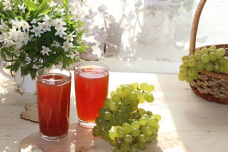 Citrus grape cider, juice and ingredients on a sunny table. The concept of detox diet and weight loss, healthy and natural food. Summer drinks, vitamins C,
