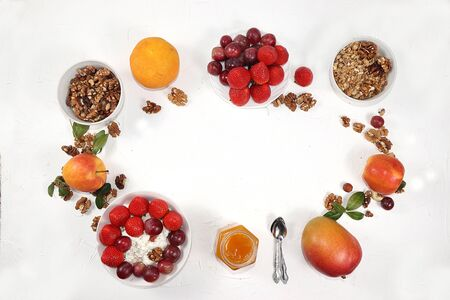Strawberry yogurt, granola, cottage cheese, honey, mango, strawberries and grapes on a light table. The concept of healthy and natural food. Useful breakfast, food for children, selective focus, top view