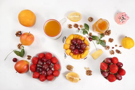 Useful breakfast, food for children, Strawberry yogurt, granola, cottage cheese, honey, mango, strawberries and grapes on a light table. The concept of healthy and natural food. selective focus,