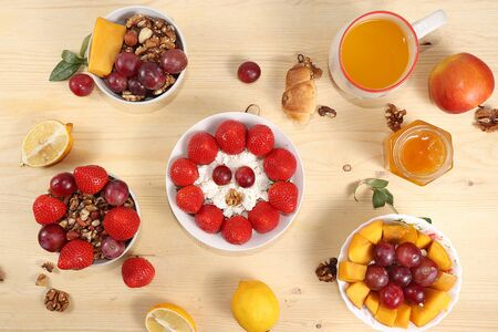 Useful breakfast, food for children, Strawberry yogurt, granola, cottage cheese, mango, strawberries and grapes on a light table. The concept of healthy and natural food. selective focus